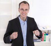 Successful businessman with suit and closed fists smiling at off Stock Photos