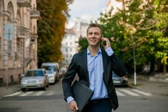 Successful businessman in suit with laptop in the city royalty free stock photos