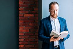 Successful businessman in a suit sits, stands and reads a book in the office. Adult successful businessman in a suit sits, stands and reads a book in the office stock photo