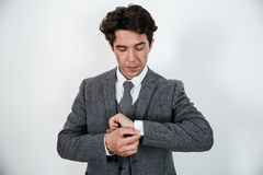 Successful businessman in suit standing and buttoning cuff sleeves. Isolated over white Stock Photo