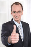 Successful businessman with suit and tie smiling and thumbs up a Royalty Free Stock Photography
