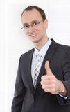 Successful businessman with suit and tie smiling and thumbs up a Stock Photography