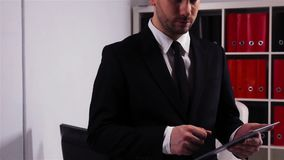Successful businessman with tablet computer in office. Successful businessman with ipad in office, super slow motion, 240fps. He look at camera and smiling stock video footage