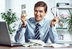 Successful businessman takes off his glasses and showing money. Photo of young man working in the office. Business concept Stock Images