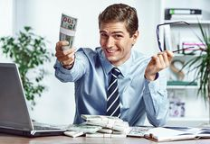 Successful businessman takes off his glasses and showing money. Photo of young man working in the office. Business concept Stock Photography