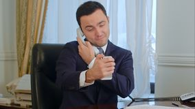 Successful businessman taking a funny selfies by his smartphone and then having a landline phone call. Professional shot in 4K resolution. 055. You can use it Royalty Free Stock Photo