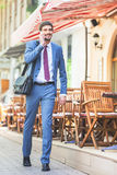 Successful businessman talking by mobile phone and walking Royalty Free Stock Image