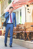 Successful businessman talking by mobile phone and walking. At street near french cafe. Early morning. Urban, city life. Happy intelligent man Stock Image