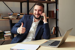 Successful businessman talking on the phone and showing thumbs u Royalty Free Stock Photography