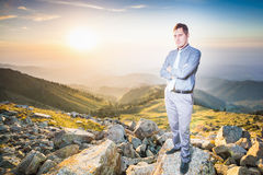 Successful businessman at top of mountain looking at camera Royalty Free Stock Photo