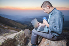 Successful businessman on top of mountain, using a laptop. Image of achieve and successful businessman on the top of mountain, using a laptop for online payment Royalty Free Stock Photo