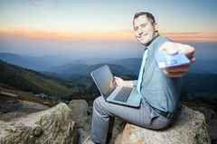Successful businessman on top of mountain, using a laptop. Image of achieve and successful businessman on the top of mountain, using a laptop for online payment Royalty Free Stock Images