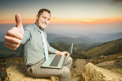 Successful businessman on top of mountain, using a laptop. Image of achieve and successful businessman on the top of mountain, using a laptop with thumbs up Stock Photos
