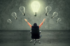 Successful businessman under lightbulb. Successful businessman sitting on chair under lightbulb Stock Photos