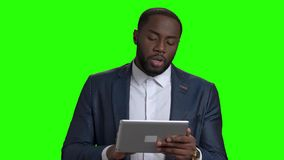 Successful businessman using digital tablet on green screen. African american guy in formal wear looking at digital tablet and speaking on chroma key stock video footage