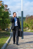 Successful businessman walking in a park Royalty Free Stock Photo