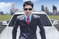 Successful businessman wearing sunglasses in front of luxury car with cityscape background.  Royalty Free Stock Photo