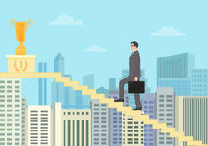 Successful businessman winner climbing the stairs to the Gold Cup Award on City background. Royalty Free Stock Photography