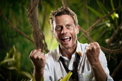 Successful businessman winning challenges. Successful winning businessman in torn clothing smiling with fists raised in the jungle Stock Images