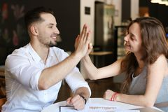 Successful businessman and woman working with documents, giving high five. stock image
