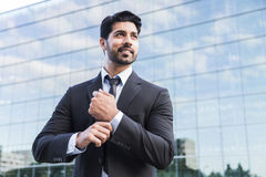 Successful businessman or worker standing in suit and straightens shirt. Arabic serious smiling happy successful positive businessman or worker in black suit Royalty Free Stock Photos