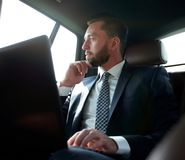 Businessman working with laptop and looking out the window of a car Royalty Free Stock Photos