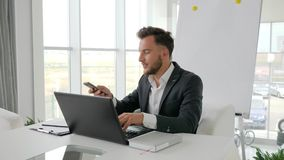 Successful businessman Works on laptop at Internet in boardroom, happy executive talk on smartphone stock video footage