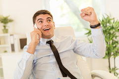Successful Businessman. Successful young businessman using phone in the office with raised arms celebrating success Stock Images