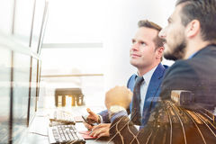 Successful businessmen in office. Business success. Successful businessmen trading stocks. Equity traders looking at on multiple computer screens in conteporary Royalty Free Stock Image