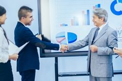 Successful businessmen shaking hands greeting each other on the. Successful businessmen shaking hands greeting each other royalty free stock images