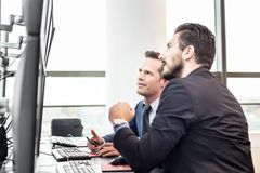 Stock traders looking at market data on computer screens. Successful businessmen trading stocks. Stock traders looking at graphs, indexes and numbers on Royalty Free Stock Photography