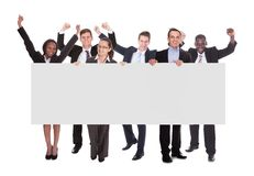 Successful businesspeople holding blank billboard. Full length portrait of successful businesspeople holding blank billboard over white background stock photo