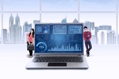 Successful businesspeople lean on laptop Stock Images