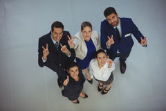 Successful businesspeople showing victory sign. In office Royalty Free Stock Images