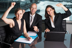 Successful businesspeople. Three persons in a panorama office celebrating royalty free stock images