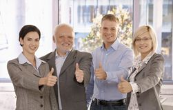 Successful businessteam giving thumbs up. Standing in bright office, smiling Stock Photography