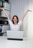 Successful businesswoman. Smiling businesswoman stretching arms in air, sat behind laptop computer in office Stock Photography
