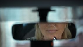 Successful businesswoman applying lipstick and looking in rear view car mirror. Stock footage stock video