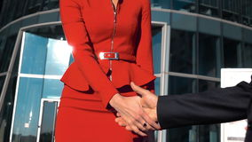 Successful businesswoman and businessman shaking hands outdoor. Young sexy successful brown hair businesswoman with glasses in red dress suit and businessman stock video footage