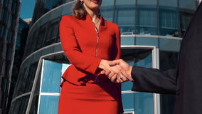 Successful businesswoman and businessman shaking hands outdoor. Young sexy successful brown hair businesswoman with spectacles in red dress suit and businessman stock footage