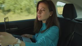 Successful businesswoman in car hurry up to work. Attractive female business executive in formal wear with laptop pc being late for business meeting, checking stock video