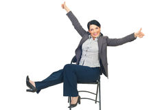 Successful businesswoman on chair gives thumbs Stock Photo