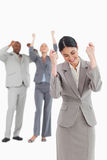 Successful businesswoman with cheering associates behind her Royalty Free Stock Photography