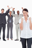 Successful businesswoman with cheering colleagues behind her Stock Image