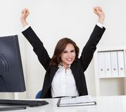 Successful Businesswoman At Desk. Portrait of a successful young businesswoman with clenched fists at computer desk Royalty Free Stock Photos