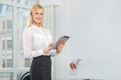 Successful businesswoman or entrepreneur taking notes in tablet. Royalty Free Stock Photo