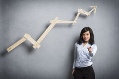 Successful businesswoman in front of positive trend graph. Royalty Free Stock Photo
