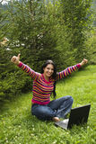 Successful businesswoman give thumbs up. Beautiful happy woman sitting with legs crossed ,bare feet  and working on laptop in vacation at mountain with fir trees Stock Photo