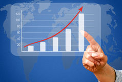 Businesswoman and upward trend graph. Hand of businesswoman touching upward trend graph on touchscreen with world map in background Stock Photo