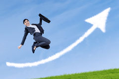 Successful businesswoman jumping with arrow sign Royalty Free Stock Photography